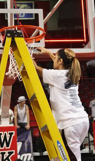Eighth grader Haeli Howard cuts down a piece of the net after the Lady Knights captured the state championship.