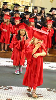 Madelyn Shannon wipes her nose with her graduation gown as she leaves the graduation ceremony. Irene Chea is pictured behind her.