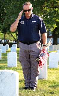 First Lieutenant Nick Birt of Danville salutes the grave of a soldier buried at the Lebanon National Cemetery. Birt is the squadron commander of the Civil Air Patrol in Danville.