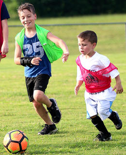Keegan Cheser (left) and Carter Pruitt (right) chase after the ball during the Marion County High School girls soccer team's camp last week at Marion County High School.
