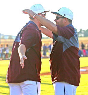 Marion County Assistant Coaches Jason Buckman (left) and Toby Tungate (right) share a hug after the Knights clinch their first ever regional title and earn a trip to the state tournament last Wednesday against the Cardinals.