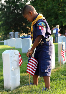 Derrick McCormick, 5, of Lebanon helps decorate graves at the Lebanon National Cemetery with fellow members of Cub Scouts Pack 90 on Saturday morning, May 25.