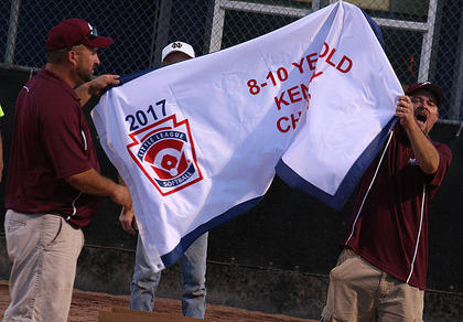 Assistant Coach Terry Cox (left) and Head Coach Jim Reed (right) celebrate with the banner after the 9-10 All-Stars clinched the state title.