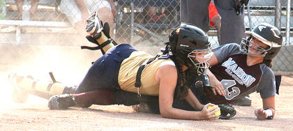 Lily Thompson slides across home plate in Marion County's 10-0 win over North Oldham. The catcher dropped the ball to allow Thompson to score the final run that clinched the state title for Marion County.