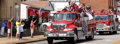 The Marion County 10-12 All-Stars, with the 8-10 All-Stars behind them, make their way down Main Street in a victory parade. The 10-12 All-Stars defeated North Oldham 10-0 for the state title and a spot in the regional tournament.