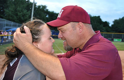 Reece Caldwell (left) and Head Coach Jim Reed (right) embrace in celebration after Caldwell's put out to third base to clinch the championship against Boyd County.