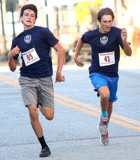 Blake Thompson (left) and Justin Elder (right) race to cross the finish line first at the Pokey Pig 5K Saturday. Thompson beat Elder by a half second.