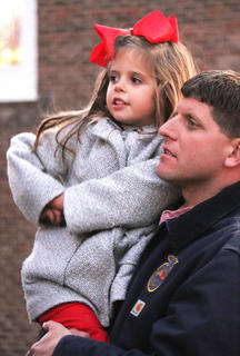 Daniel Mattingly holds his daughter, Amelia, while they listen to chorus students sing Christmas carols on the steps of the Marion County Heritage Center Friday evening.