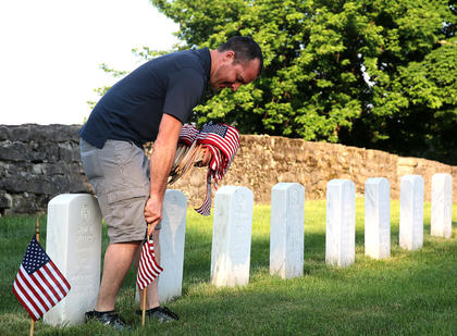 Mike Medley helps decorate graves at the Lebanon National Cemetery Saturday morning, May 25.