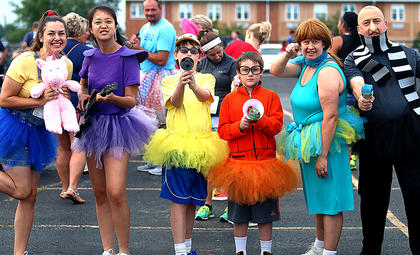 The Despicable Me crew is excited as they prepare for the Back Tutu School walk/run on Saturday. Pictured, from left, are Harmony Lanham, Kelly Suh, P.J. Lanham, Kenneth Lanham, Amanda Lanham and Patrick Lanham. The group won an award for having the best theme. The Leathers family – dressed as Smurfs - also won an award for best theme.