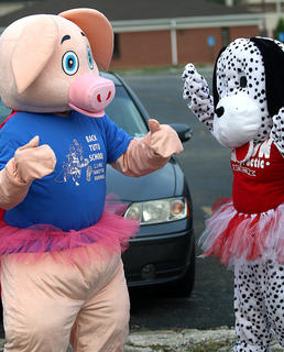 Marion County Country Ham Days mascot Piggles and Bones from Dr. Rod Coxon's office dance to music while waiting for runners to cross the finish line.