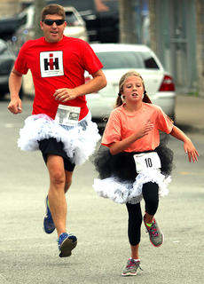 Gracie Mattingly finishes strong as her father, Daniel, follows behind.