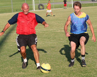 MCHS Boys Soccer Head Coach Greg Conley, left and Lance Masterson, who graduated last year, battle for possession of the ball during the alumni game on Friday.
