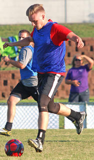 Conner Mattingly keeps his eye on the ball as he drives it up the field during Friday's alumni soccer game.