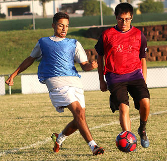 Alan Guzman, left, controls the ball as Oswaldo Cruz looks to steal it during the alumni soccer game Friday evening.