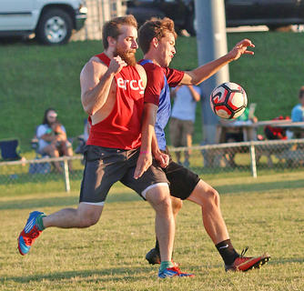 """Jacob """"Beans"""" Giles (in red) and Dalton Hammond (in blue) put up a stout fight for the ball during the alumni match on Friday."""