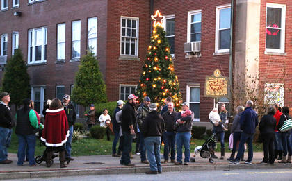 A crowd gathers around the community Christmas tree outside the Marion County Heritage Center Friday evening.