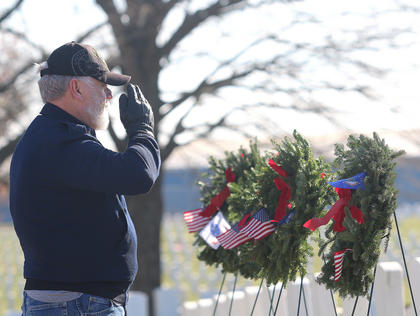 Fred McClure salutes after he presents a special wreath in honor of the United States Air Force.
