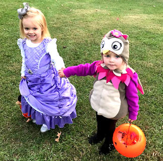 Lydia Beard, dressed as Sophia The First, and Madelyn Shannon, dressed as an owl, go trick-or-treating hand in hand.