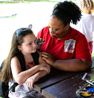Daisy Bohannon gets her face painted by the Marion County Public Library staff during the end of Summer Dream Academy celebration recently.
