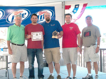 Bourbon Barrel BBQ won the grand champion trophy at the 2011 Heart of Kentucky Bourbon and BBQ Musicfest. Picture are the team members, Brian Morales, Chief Cook Andrew Armstrong, and Chris Granger. Event organizer Kenny Marrett is on the right.
