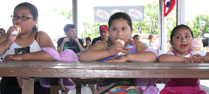 From left, the Garcia sisters, Odalis, Johanna and Ashley, enjoy ice cream while listening to music under the farmer's market pavilion.