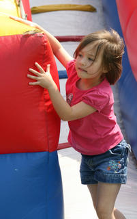 Brooklyn Thomas, 5, plays on the bouncy slides set up near the Cardinal Den on Saturday morning.