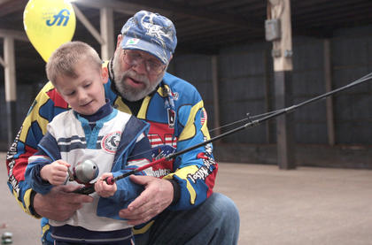 Steven Sargent, 4, of Danville gets a casting lesson from Shelton Young at the Fishing For Kids booth.