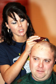 Pat Thompson gets cleaned up by Mindy Garrett. Thompson is the father of this year's ambassador child, Logan Thompson.