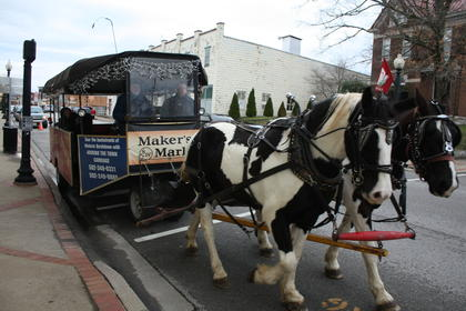 The horse-drawn trolley takes off after picking up a load of passengers.