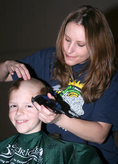 The 2006 ambassador child, Matthew Miles, returned for another haircut this year. Sherry Moore does the shaving.