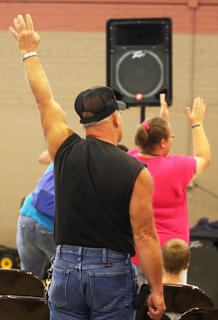 Members of the crowd raise their hands in worship during a musical performance by Spirit Seekers Saturday.