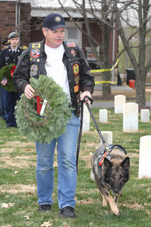 Sgt. Beyco WMD Retired Marine Military Service Animal and his handler lays a remembrance wreath in memory of those who served and are serving in the United States Marine Corps.