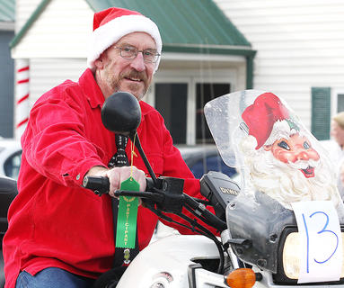 Blake Ohsol rides a holiday-decorated motorcycle in the parade.