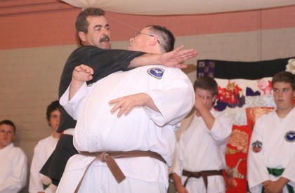 John Cox demonstrates a self-defense technique with assistance from Aaron Phipps.