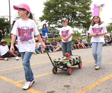 Alyssa Followay (pulling the float), McKenzie Bright, and Bailey Thompson travel the parade route.