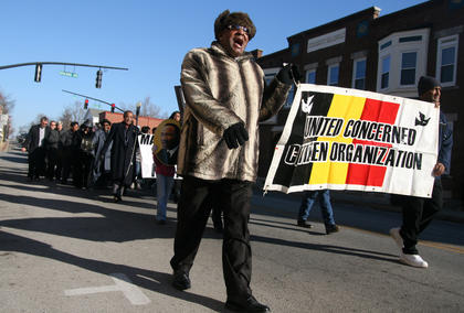 Charlie Bell and John Bell lead the march, carrying the banner for the United Concerned Citizens Organization.