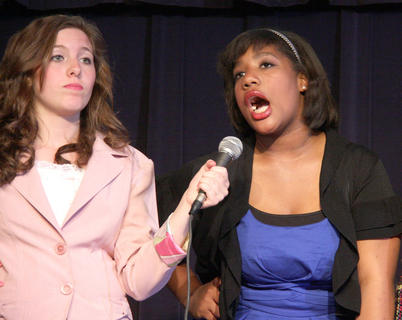Violet Beauregard (Shaniqua Young, right) smacks her gum during an interview with Phineous Trout (Rebecca Evans)