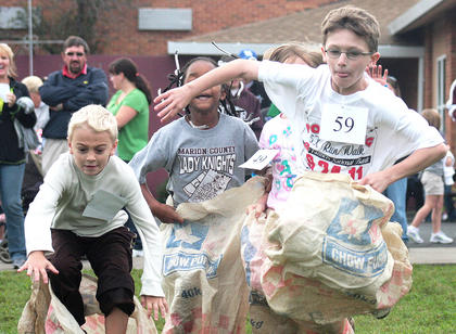 Cameron Martin hops into the lead in one of the sack races Saturday morning at St. Augustine.