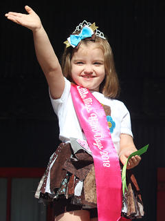 Sadie Kate Jewell, 3, waves to the crowd after winning this year's Little Miss Ham Days competition on Saturday morning.