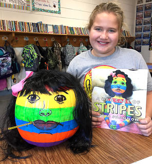 "West Marion Elementary School student Addilynn Bartley is pictured with her Camilla Cream-themed pumpkin from the book ""A Bad Case of Stripes."""