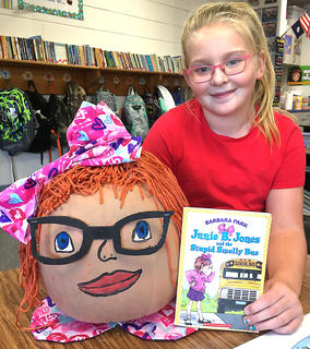 "West Marion Elementary School student Addison Edelen is pictured with her Junie B. Jones-themed pumpkin from ""The Stupid Smelly Bus"" book."