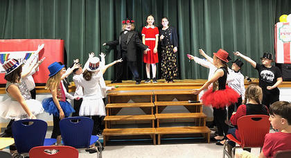 "Pictured, from left, are Samuel Wiser (Daddy Warbucks), Evelyn Mattingly (Annie) and Harper Blake (Grace) performing a portion of the musical, ""Annie."""