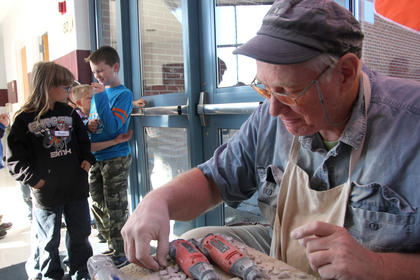 Al Hardin prepares to grind limestone pieces for LES students.