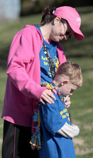 Laura Essex stands with her son, Peyton, after placing a medallion around his neck.
