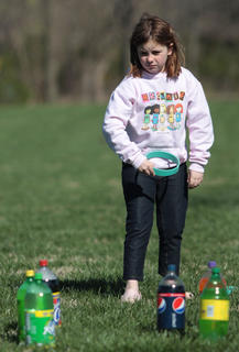 Emma Doheny, 7, prepares to toss a ring around a two-liter bottle.