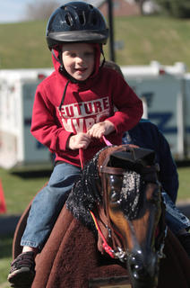 Caden Broyles, 4, of Lebanon tries the equicizer during Saturday's event. Riding Enhanced Around Therapeutic Horses Center of Campbellsville brought the mechanical horse to the event.
