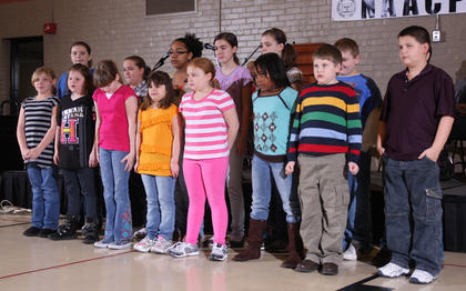 "Students from Glasscock Elementary School sang uplifting songs, including ""We Shall Overcome,"" during the event."