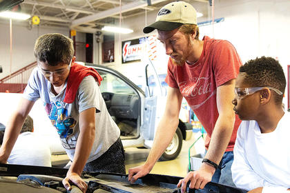 Brian Deacon (center)showsChad Braggand David Smalley the mechanics of a car. The Car 101 camp was held at the Marion County Area Technology Center June 3-5.