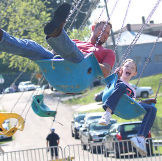 Clayton Watson (left) and his daughter Audrey Watson (right) enjoy a ride on Swagger at the Ham Days carnival on Saturday.